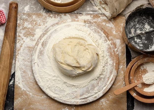 Der geknetete teig aus weißem weizenmehl liegt auf einem runden holzbrett, einem metalleimer und einem hölzernen nudelholz, draufsicht