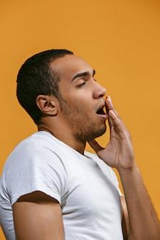 Der gelangweilte afroamerikanische mann möchte vor dem orangefarbenen raum schlafen