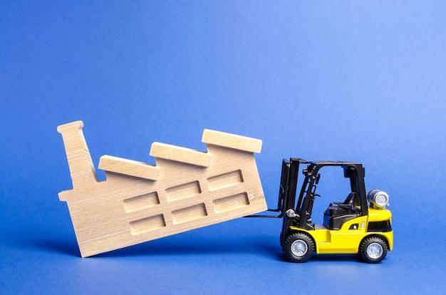 Der gelbe gabelstapler transportiert die fabrik an einen anderen standort verlagerung schädlicher industrieproduktion außerhalb der stadt