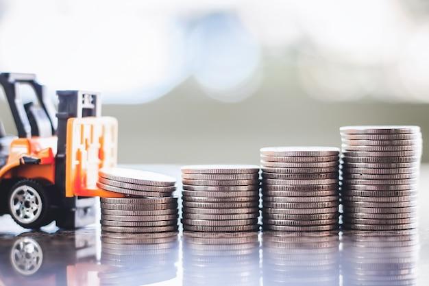 Der gelbe spielzeuggabelstapler mit stapel von münzen gegen unscharfen hintergrund für das einsparen des geldkonzeptes