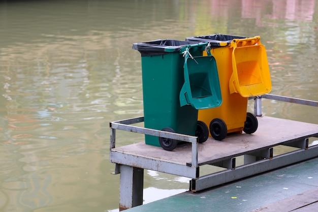 Der gelbe und grüne abfalleimer nahe dem fluss in thailand