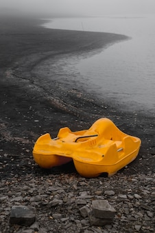 Der gelbe vergessene katamaran steht im herbst allein an der küste