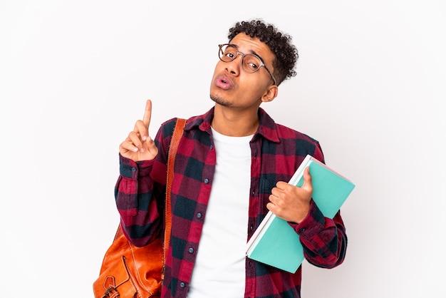 Der gelockte mann des jungen studenten isolierte das halten von büchern, die eine große idee haben. konzept der kreativität
