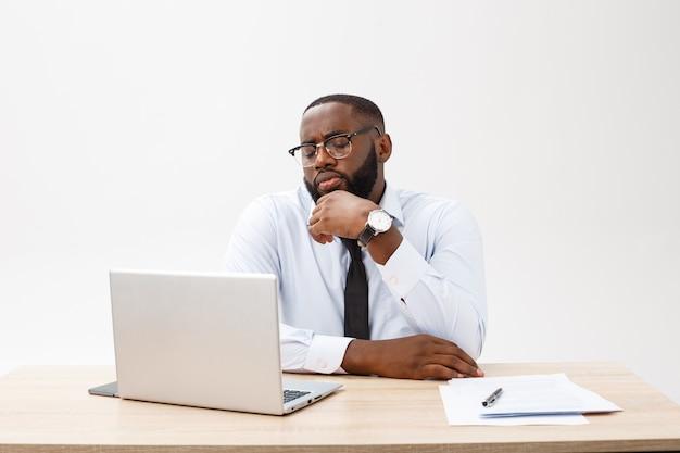 Der gereizte, dunkelhäutige junge männliche unternehmer, der sich am arbeitsplatz aufhält, fühlt sich sehr gestresst und wütend, da er nicht alle arbeiten erledigen kann