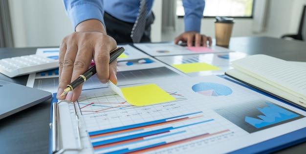 Der geschäftsmann analysiert das finanzdiagramm mit einem laptop im büro, um herausfordernde geschäftsziele für das management festzulegen und zu planen, das neue ziel zu erreichen