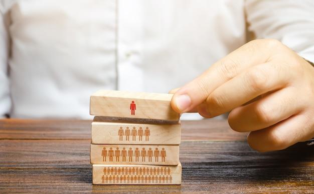 Der geschäftsmann baut eine hierarchie in einem unternehmen auf. führung, teamwork, feedback im team