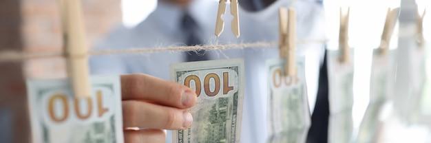 Der geschäftsmann befestigt hundert dollarnoten an wäscheklammern am seil.
