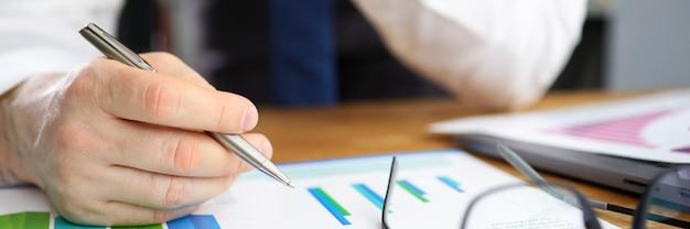 Der geschäftsmann berücksichtigt korrekturen des finanzberichts. indikatoren im kontext bestehender werbekampagnen. daten aus verschiedenen quellen auf einem bildschirm. festlegen spezifischer ziele