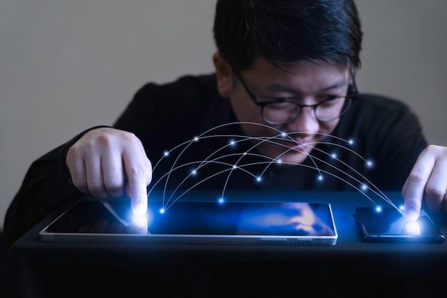 Der geschäftsmann berührt den bildschirm des tablets und des smartphones mit der datenübertragungsgrafik