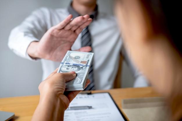 Der geschäftsmann, der ablehnt und empfängt nicht geldbanknote im umschlagangebot von den weiblichen leuten