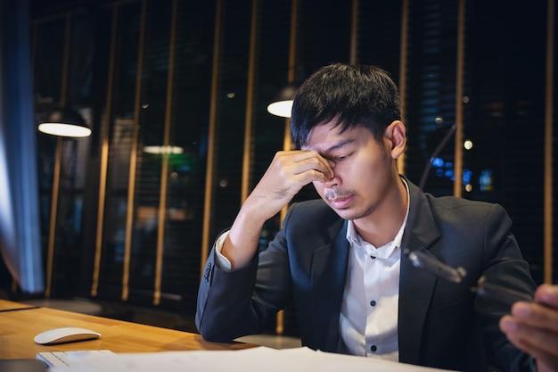 Der geschäftsmann, der die gläser müde von der computerarbeit entfernt