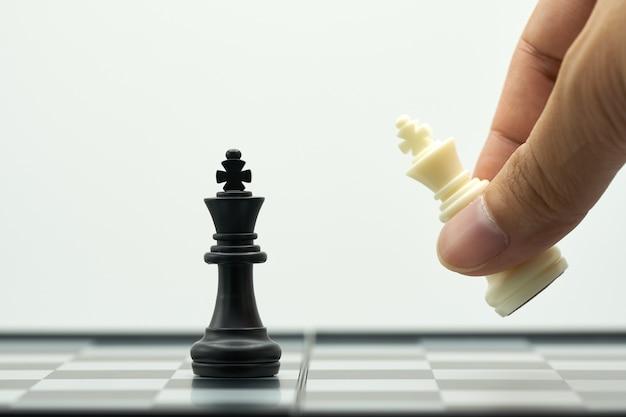 Der geschäftsmann, der ein könig-schach hält, wird auf ein schachbrett gesetzt.