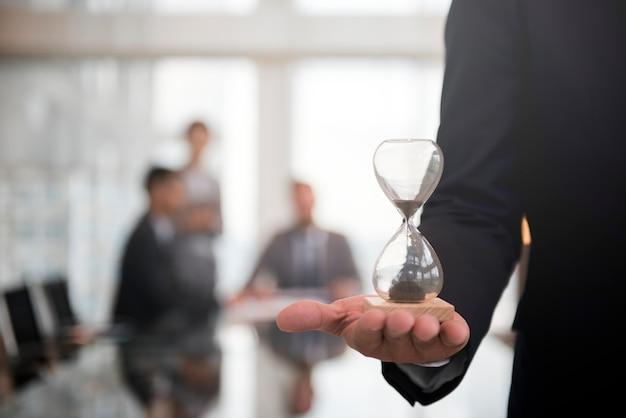 Der geschäftsmann, der ein stundenglas hält, bedeutet die wichtigkeit, rechtzeitig zu sein