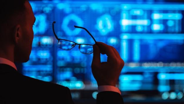Der geschäftsmann, der eine brille auf dem bildschirmhintergrund hält