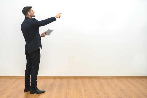 Der geschäftsmann, der eine tablette hält und auf den weißen wandhintergrund gestikuliert