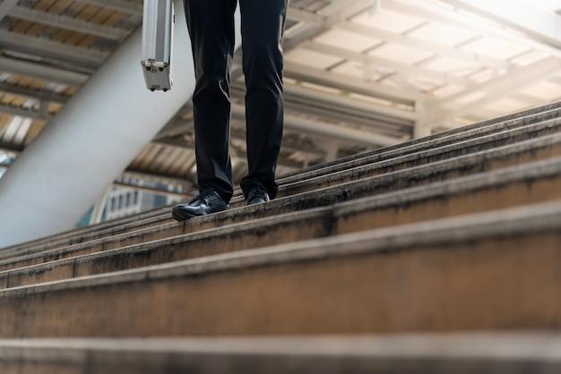 Der geschäftsmann, der einen aktenkoffer trägt, gehen herauf treppe.