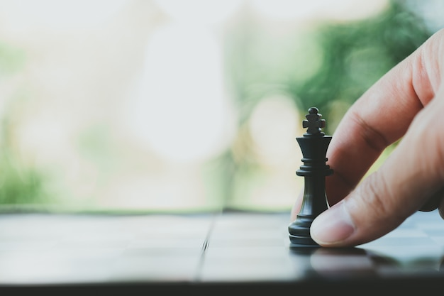 Der geschäftsmann, der einen könig chess hält, wird auf ein schachbrett gesetzt. als hintergrund verwendet