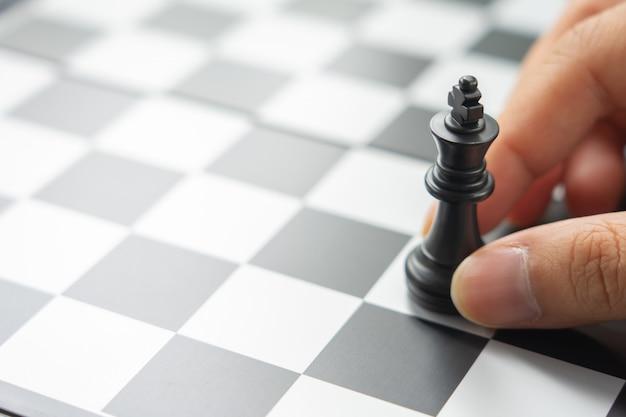 Der geschäftsmann, der einen könig chess hält, wird auf ein schachbrett gesetzt.