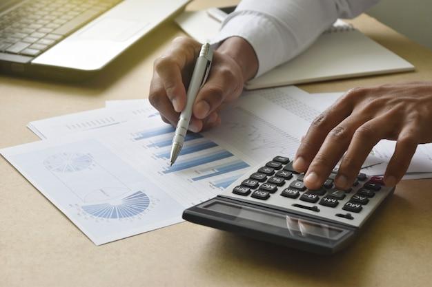 Der geschäftsmann, der finanzdiagramme und diagramme analysiert, berichten über schreibtisch im büro.