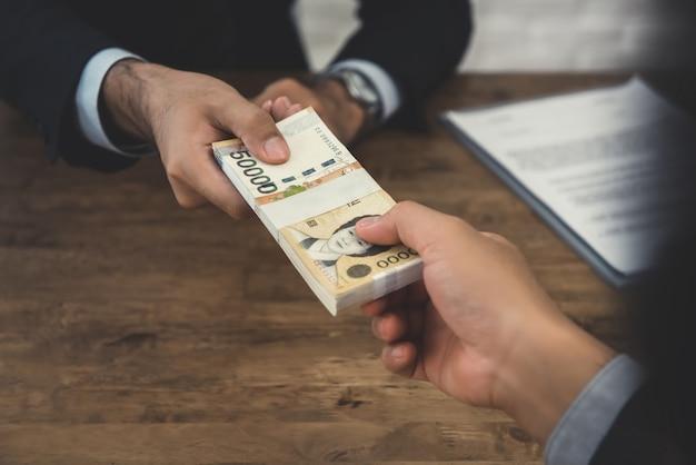 Der geschäftsmann, der geld gibt, südkoreaner gewann rechnungen, zu seinem partner am schreibtisch