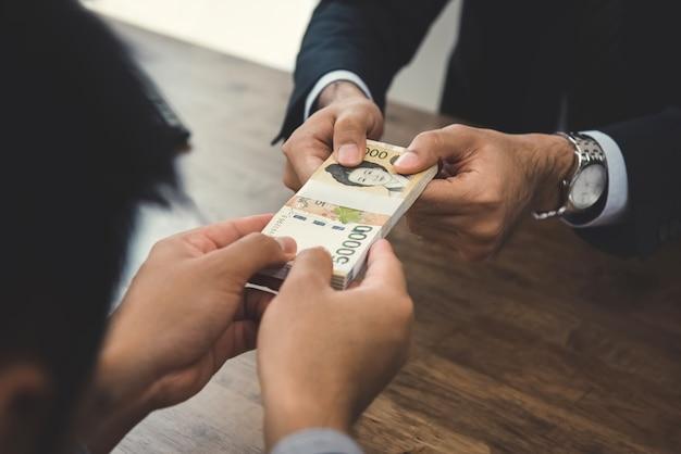 Der geschäftsmann, der geld, südkoreaner gibt, gewann währung, zu seinem partner am arbeitsschreibtisch
