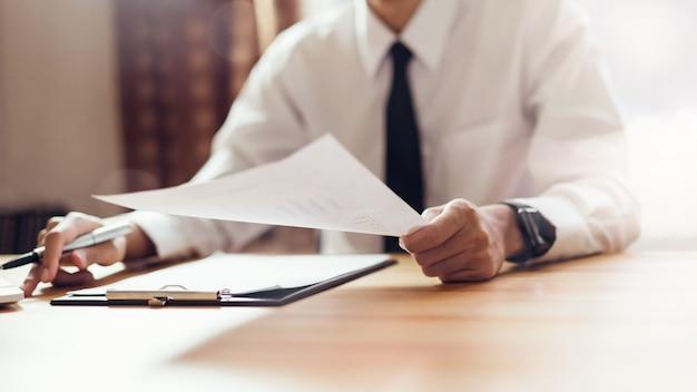 Der geschäftsmann, der im büro mit zeichen arbeitet, unterzeichnen ein dokument und einen laptop.