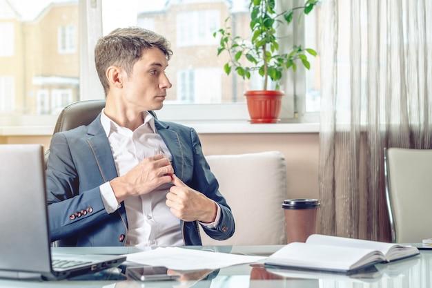 Der geschäftsmann, der im büro sitzt, versteckt ein bestechungsgeld unbemerkt in seiner tasche.