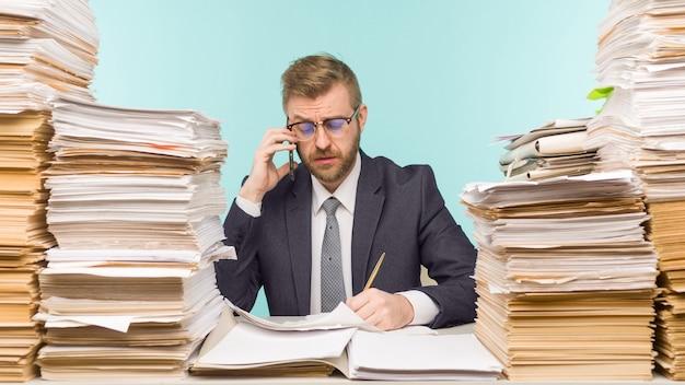 Der geschäftsmann, der im büro telefoniert und papierkram stapelt, ist mit arbeitsbildern überladen