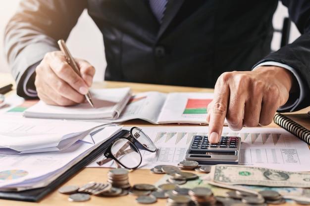 Der geschäftsmann, der im büro unter verwendung des taschenrechners für arbeitet, berechnen budgetgeld