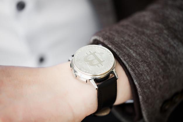 Der geschäftsmann, der in das krypowährung bitcoin investiert, hält in den händen einer sanduhr, die auf das wachstum der währung wartet