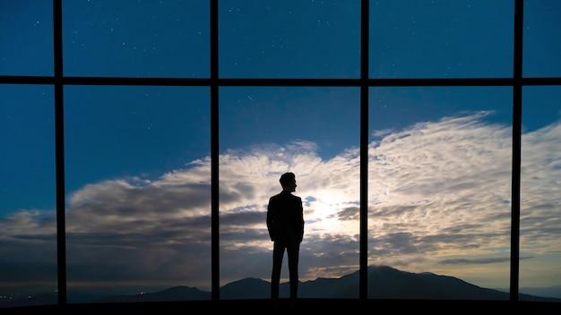 Der geschäftsmann, der in der nähe des panoramafensters auf blauem himmelshintergrund steht