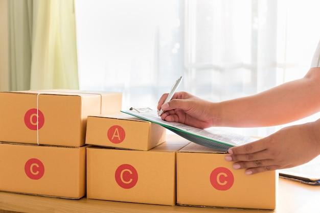 Der geschäftsmann, der mit handy arbeitet und braune pakete des kastens zu hause verpackt