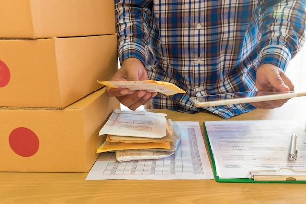 Der geschäftsmann, der mit handy arbeitet und braune pakete des kastens zu hause verpackt.