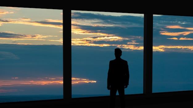 Der geschäftsmann, der nahe dem panoramafenster auf dem sonnenunterganghintergrund steht