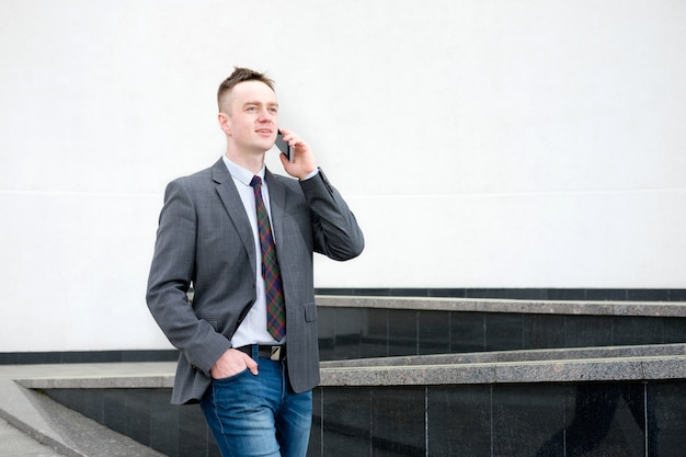 Der geschäftsmann, gekleidet in eine graue jacke, blaue jeans, ein weißes hemd und eine krawatte, kommt aus dem geschäftszentrum und telefoniert beim gehen