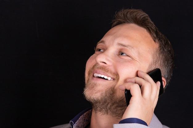 Der geschäftsmann hält ein mobiltelefon in den händen und drückt die emotionen des gesprächs aus