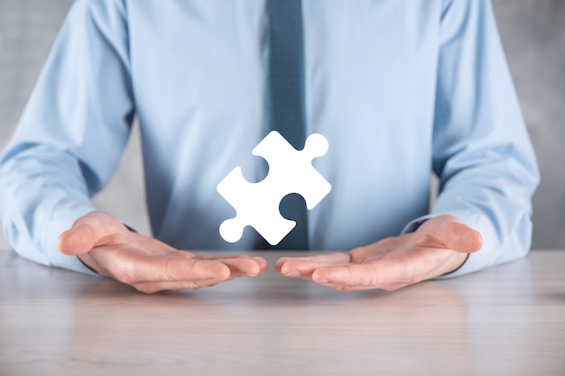 Der geschäftsmann hält ein puzzleteil in den händen