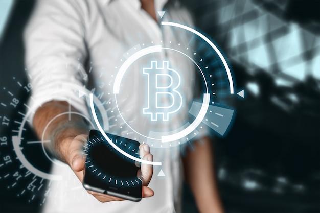 Der geschäftsmann hält ein smartphone mit einem bild des bitcoin-hologramms in der hand