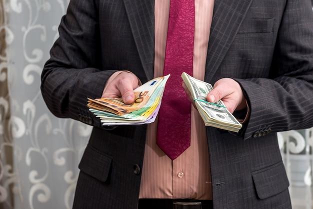 Der geschäftsmann hält eine packung dollar und euro in seinen händen