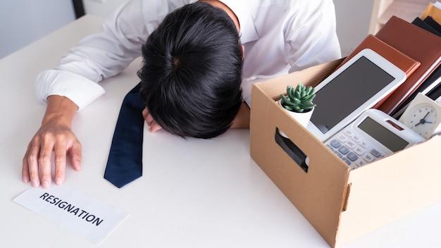 Der geschäftsmann hat den stress, zurückzutreten und das kündigungsschreiben, die änderung der arbeitslosigkeit oder das rücktrittskonzept zu unterzeichnen
