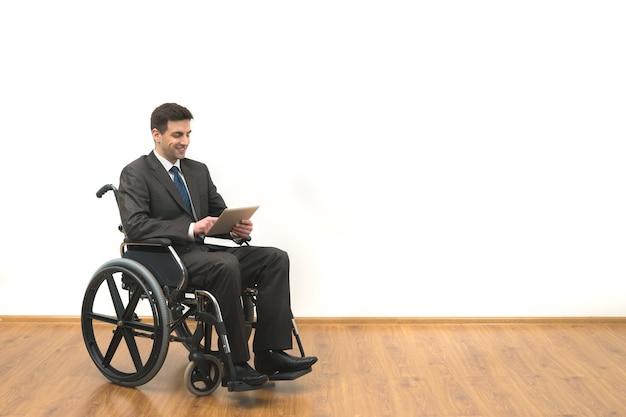 Der geschäftsmann im rollstuhl, der ein tablet auf einem weißen wandhintergrund hält