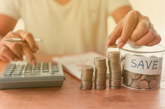Der geschäftsmann legt münzen in die ansammlung von spalten, die geldspar- oder finanzplanungsideen für die wirtschaft darstellen.