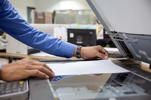 Der geschäftsmann legt papier auf den kopierer, um es zu scannen.