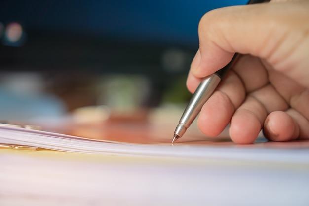Der geschäftsmann manager, der dokumente überprüft und unterzeichnet, berichtet über papiere mit taschenrechner