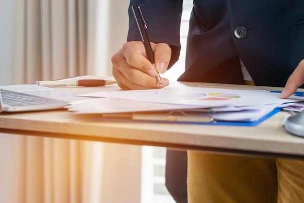 Der geschäftsmann manager, der dokumente überprüft und unterzeichnet, berichtet über papiere