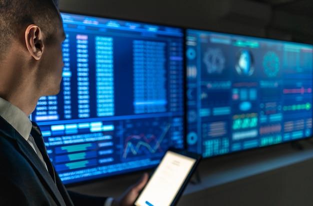 Der geschäftsmann mit einem tablet in der hand steht in der nähe des blauen bildschirms