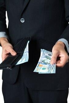 Der geschäftsmann nahm dollar aus seiner brieftasche für lohn oder spende mit weißem hintergrund.