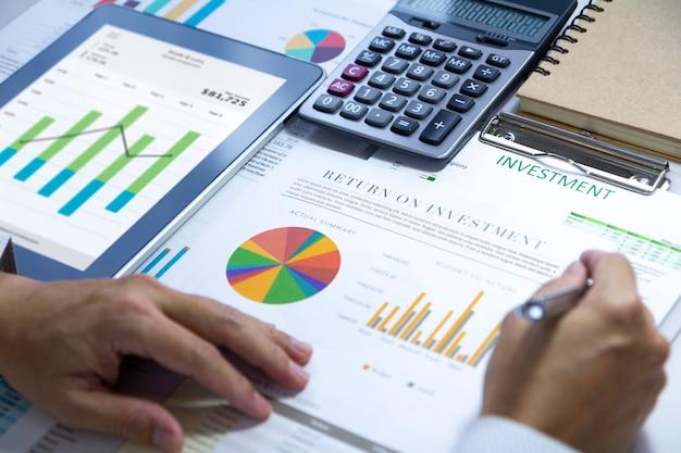 Der geschäftsmann prüft einen finanzbericht eingehend auf eine kapitalrendite oder eine analyse des anlagerisikos.