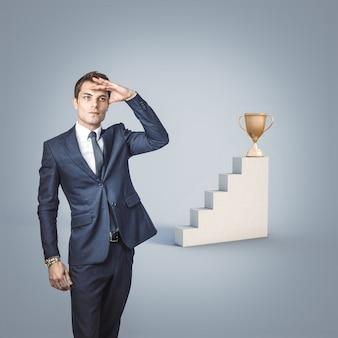 Der geschäftsmann schaut weg, um nach der auszeichnung zu suchen. konzept von erfolg und entschlossenheit.