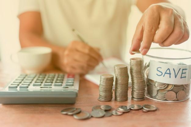 Der geschäftsmann setzt münzen ein und rechnet mit münzen, die sich in einer spalte ansammeln, die eine geldspar- oder finanzplanungsidee für die wirtschaft darstellen.